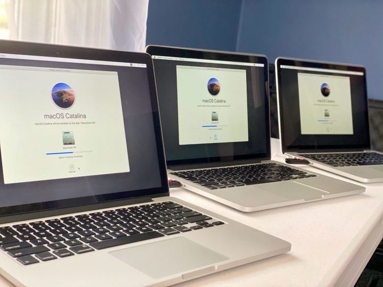 A few donated MacBook Pro laptops being set up from a fresh macOS Catalina install